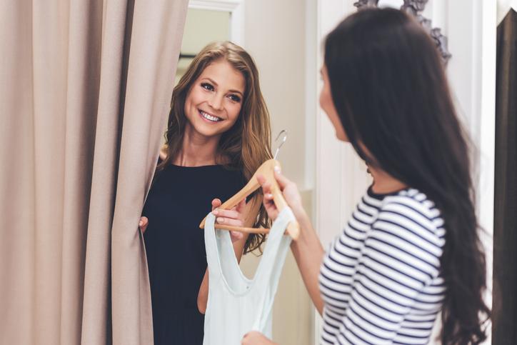 Shop employee hands dress to customer in dressing room